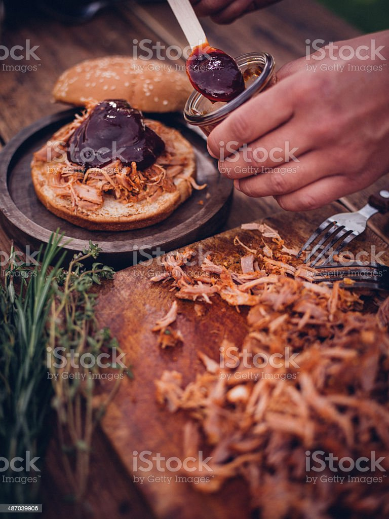 Delicious pulled pork and sauce going into a burger stock photo