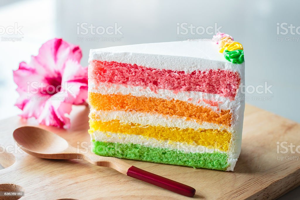 Delicious rainbow cake on wood plate. stock photo