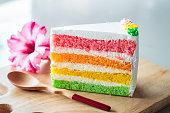 Delicious rainbow cake on wood plate.