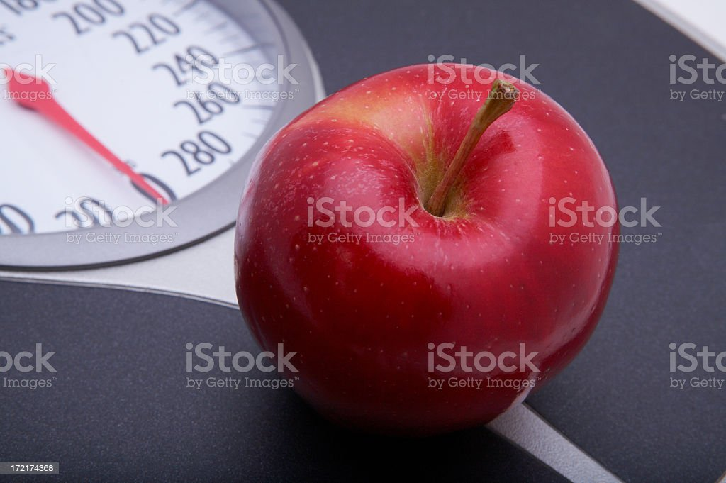 Delicious red apple on a scale royalty-free stock photo