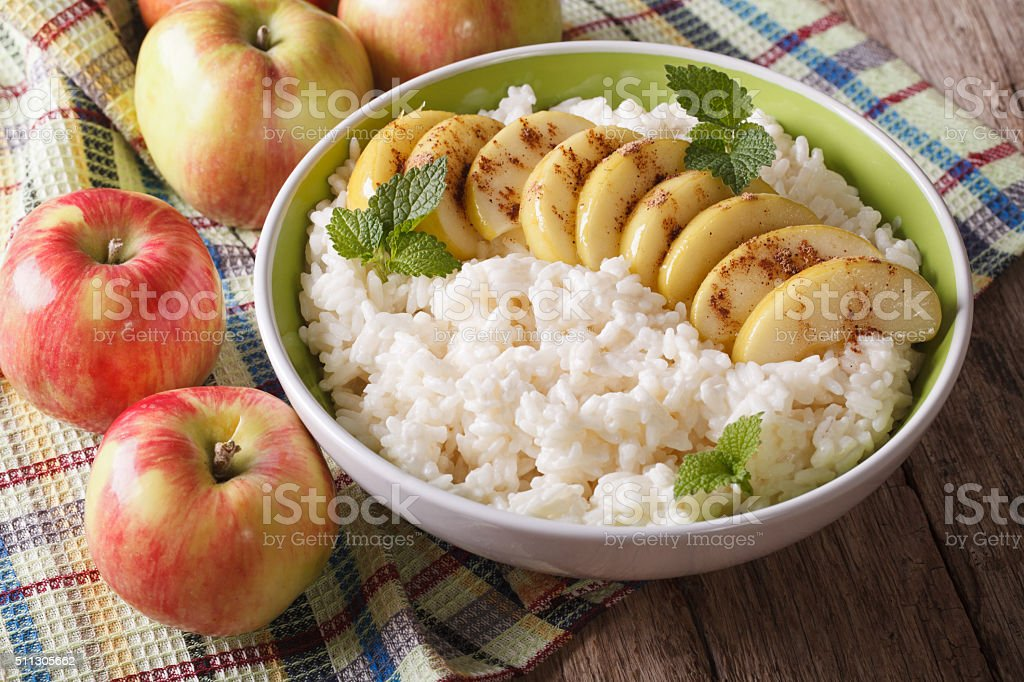 Delicious rice pudding with apples and cinnamon in a bowl stock photo