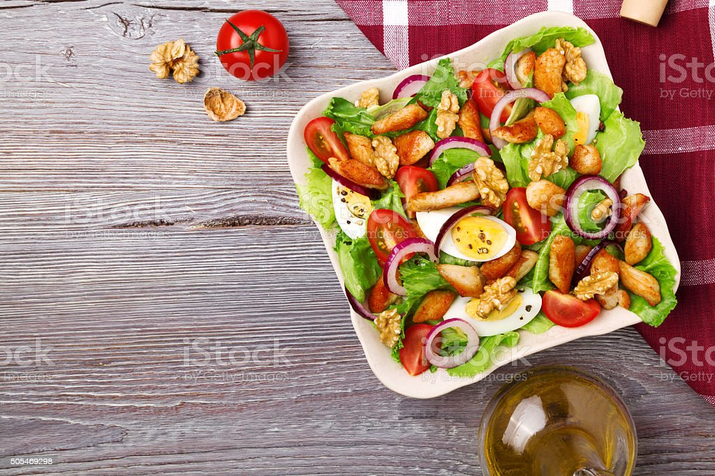 Delicious salad with chicken, nuts, egg and vegetables. stock photo