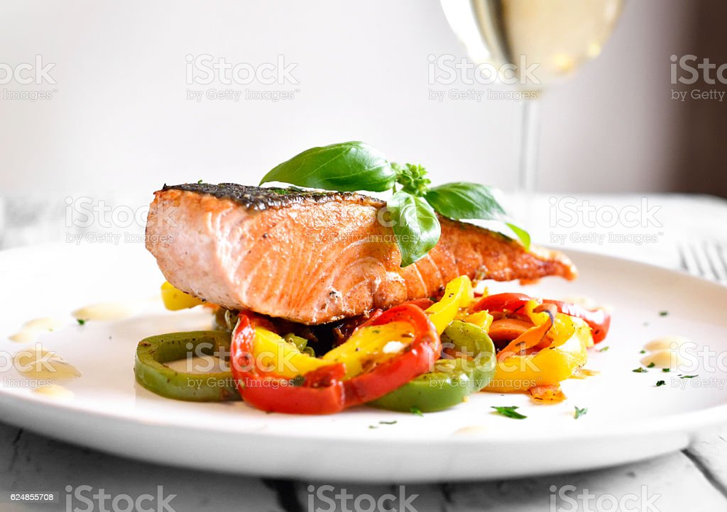 Delicious salmon filet with decorative basil leaf stock photo