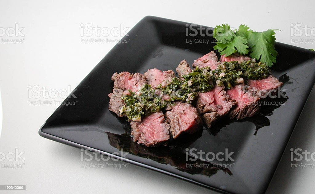 Delicious sliced steak with chimichurri sauce stock photo