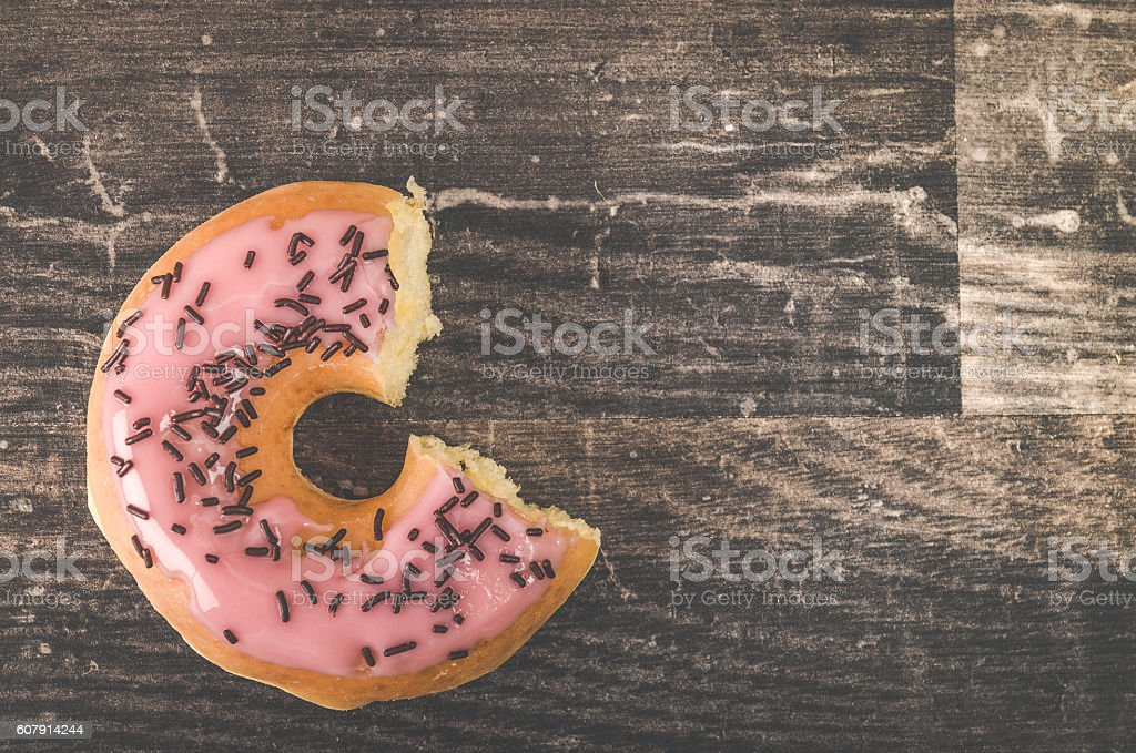 Delicious strawberry donut on a wooden table stock photo