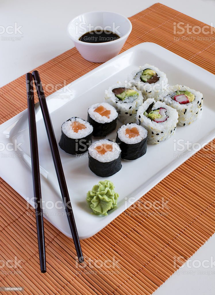 Delicious sushi rolls on white plate with chopsticks royalty-free stock photo