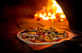 Delicious vegetarian pizza going into a wood fire oven