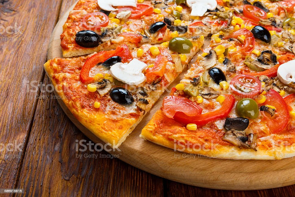 Delicious vegetarian pizza with tomatoes, mushrooms and olives stock photo