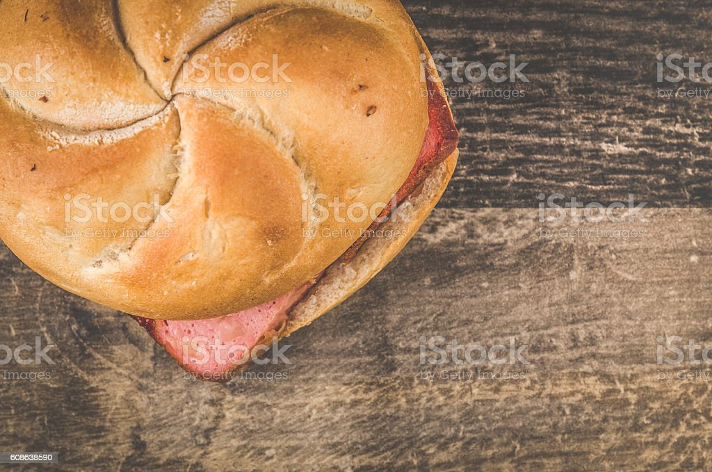 Delicious warm leberkaesesemmel on a wooden table stock photo