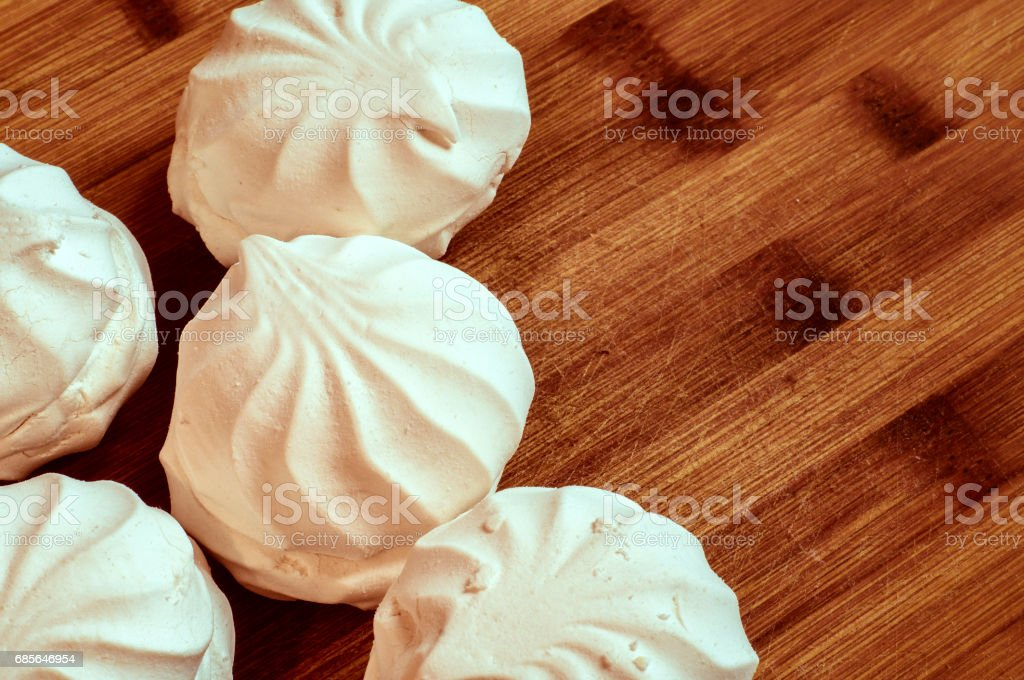 Delicious white marshmallow on a textured wooden surface. Zephyr stock photo