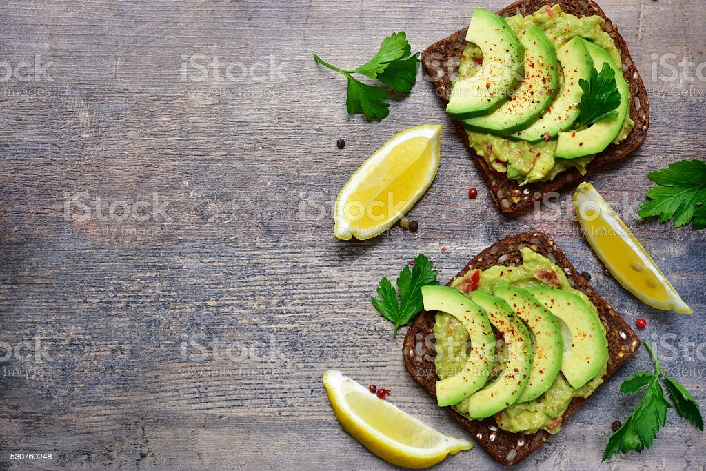 Delicious wholewheat toast with guacamole and avocado slices. stock photo