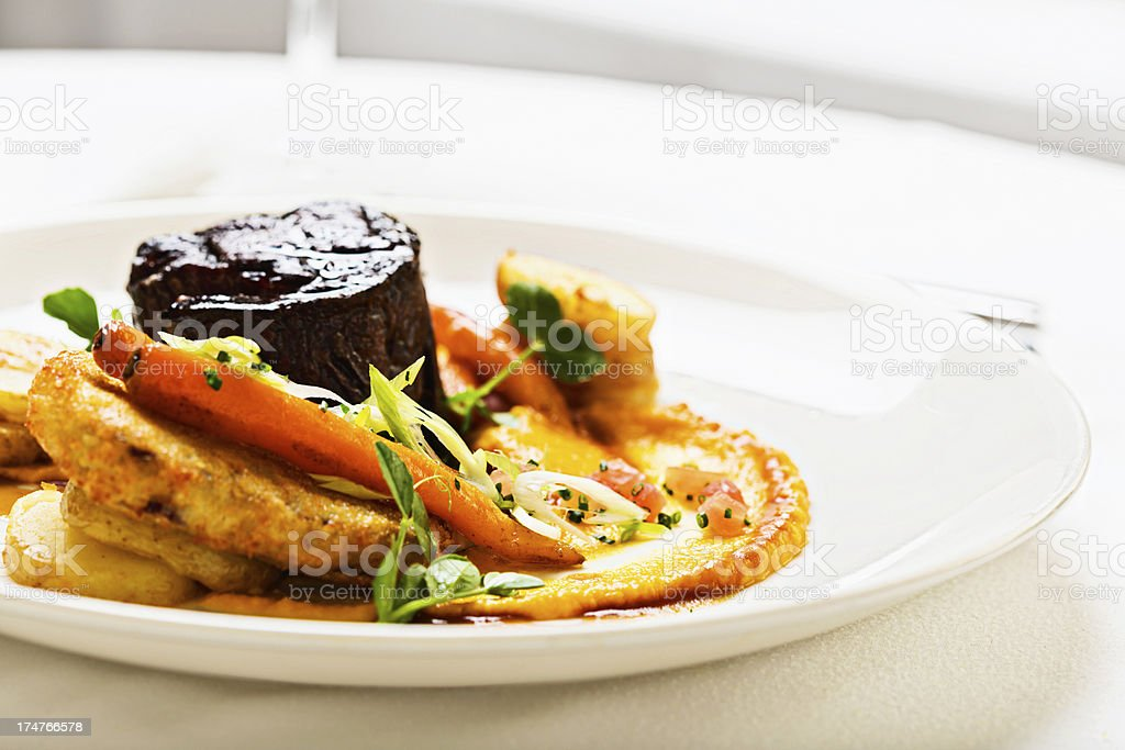 Delicious-looking filet mignon with vegetable side dishes in restaurant stock photo