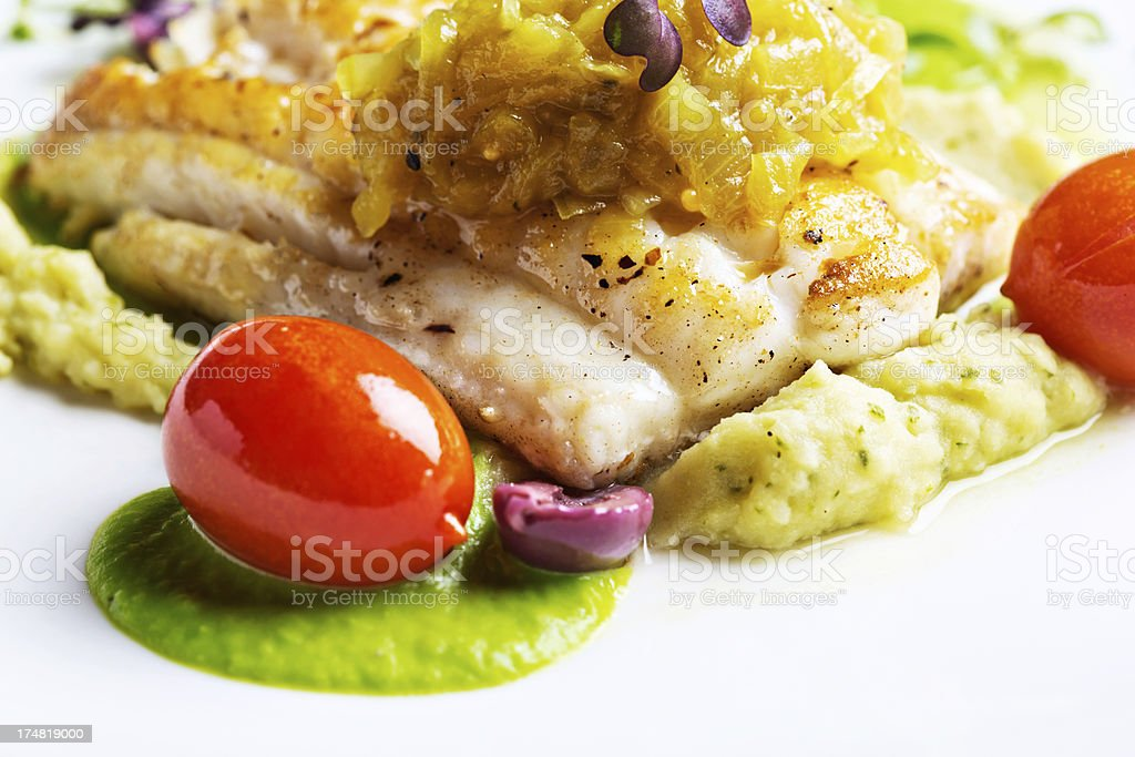 Delicious-looking restaurant meal of grilled fish and accompaniments stock photo