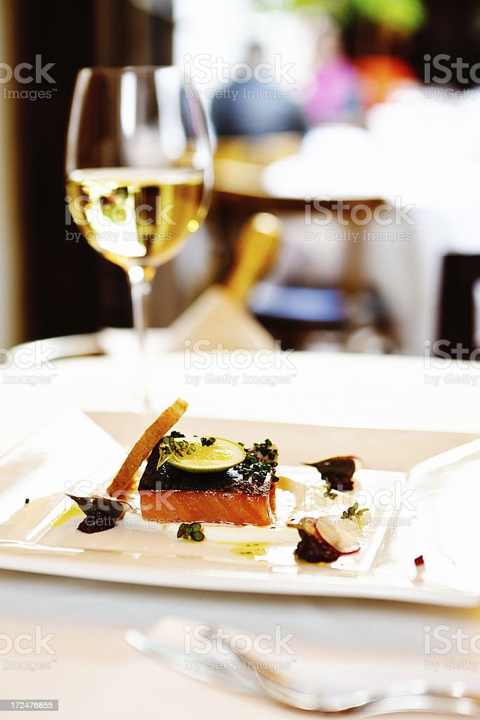Delicious-looking salmon dish and glass of white wine in restaurant stock photo