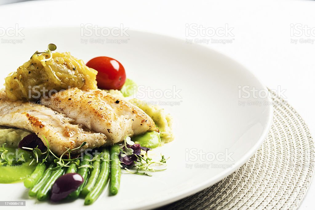 Deliciously healthy restaurant dish of grilled fish and vegetables stock photo