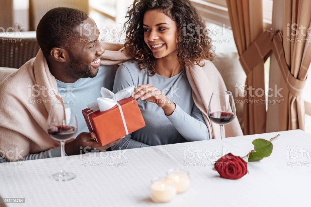 Delighted African American man giving the box to his girlfriend stock photo