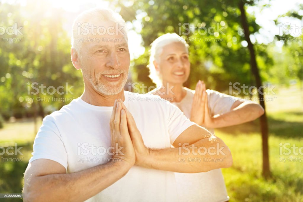 Delighted aged couple meditating in the park stock photo