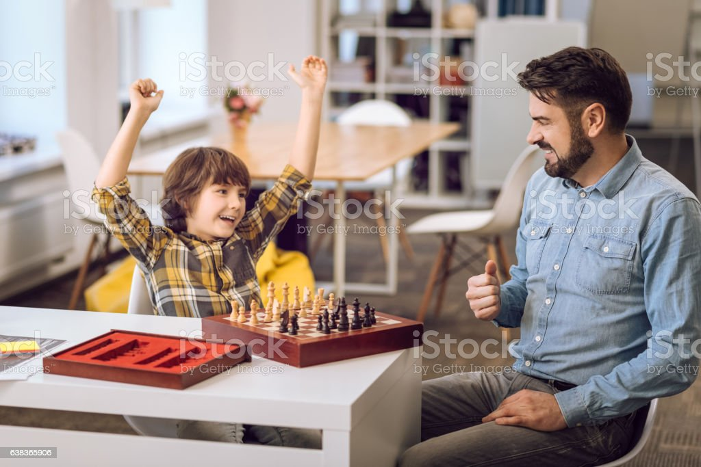 Delighted boy holding his arms upwards stock photo