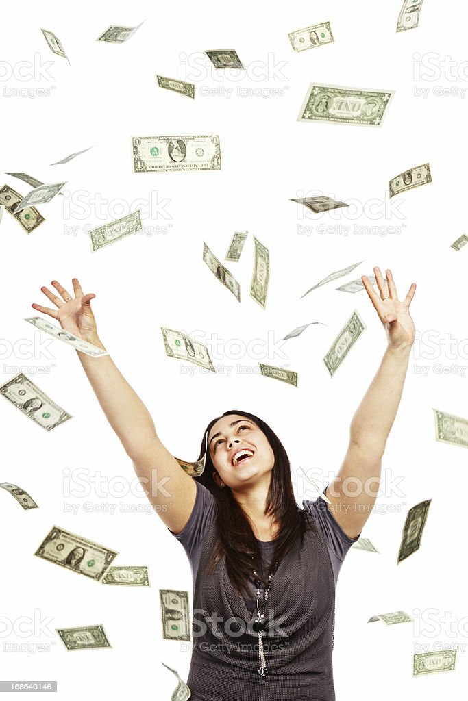 Delighted brunette tries to catch many falling dollars stock photo