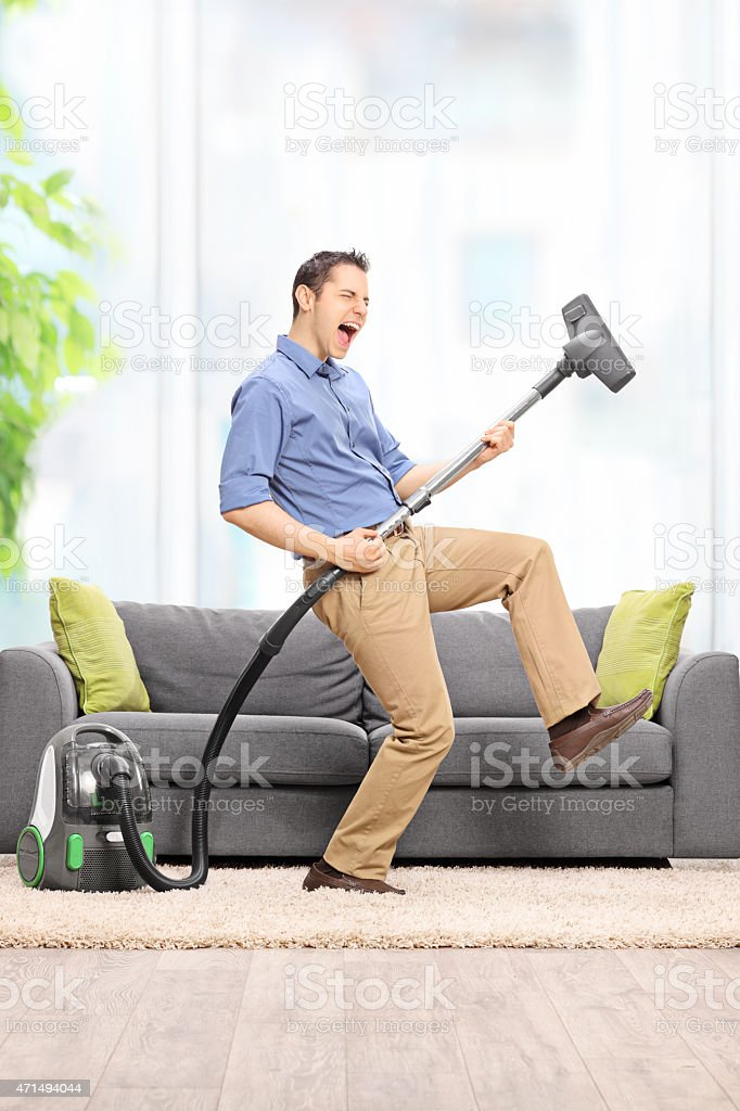 Delighted guy playing guitar on the vacuum cleaner stock photo