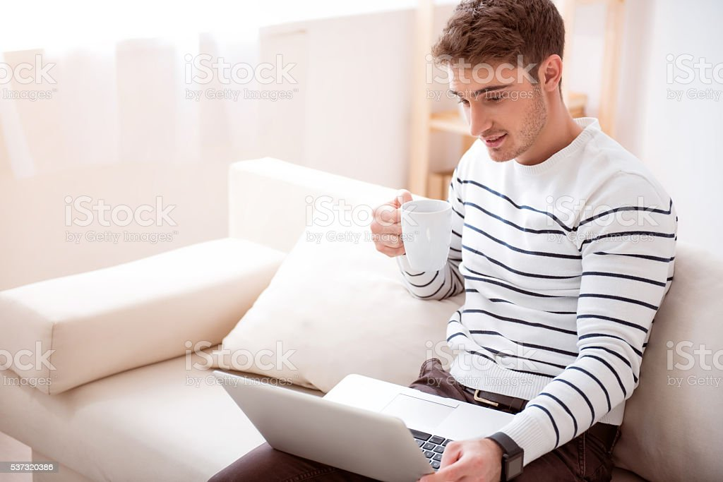 Delighted handsome man sitting on the sofa stock photo