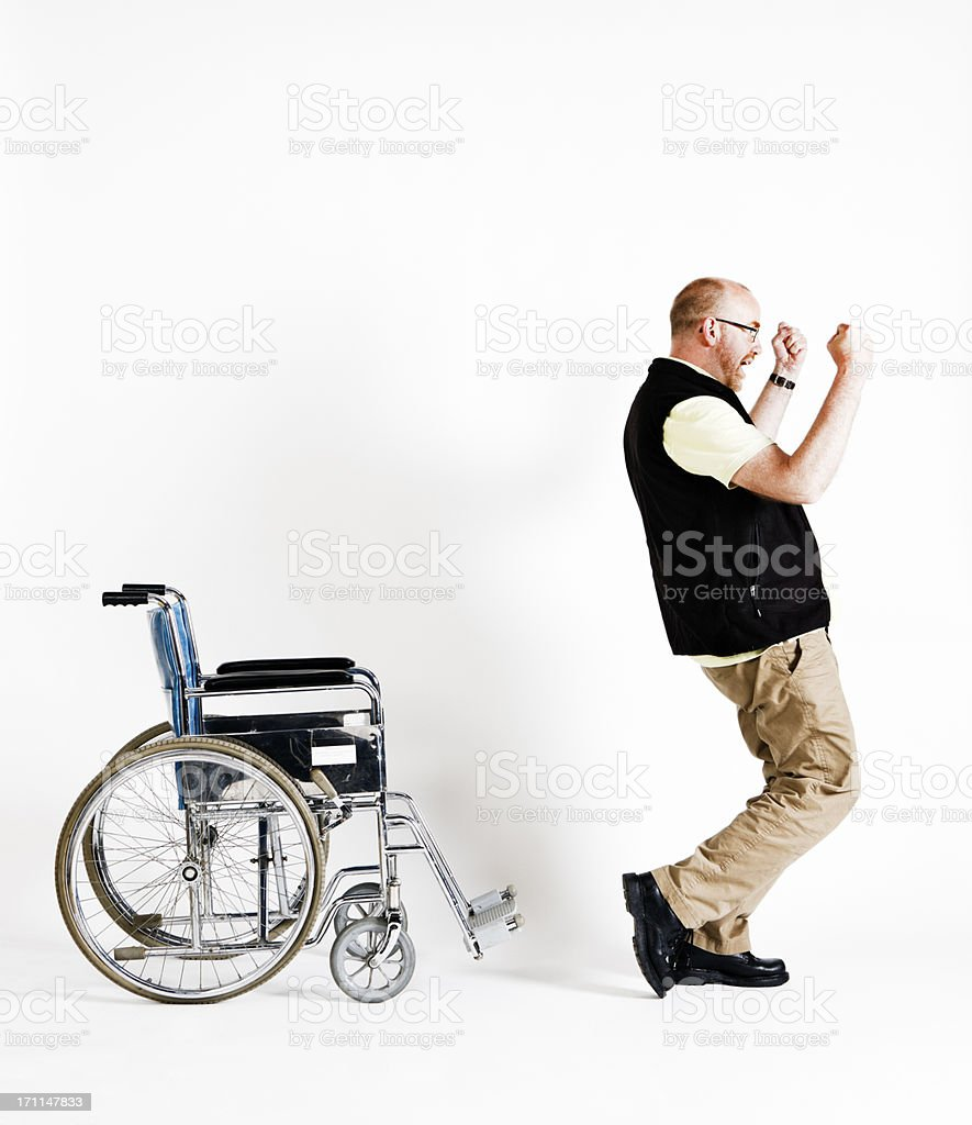 Delighted man rises from wheelchair, able to walk royalty-free stock photo