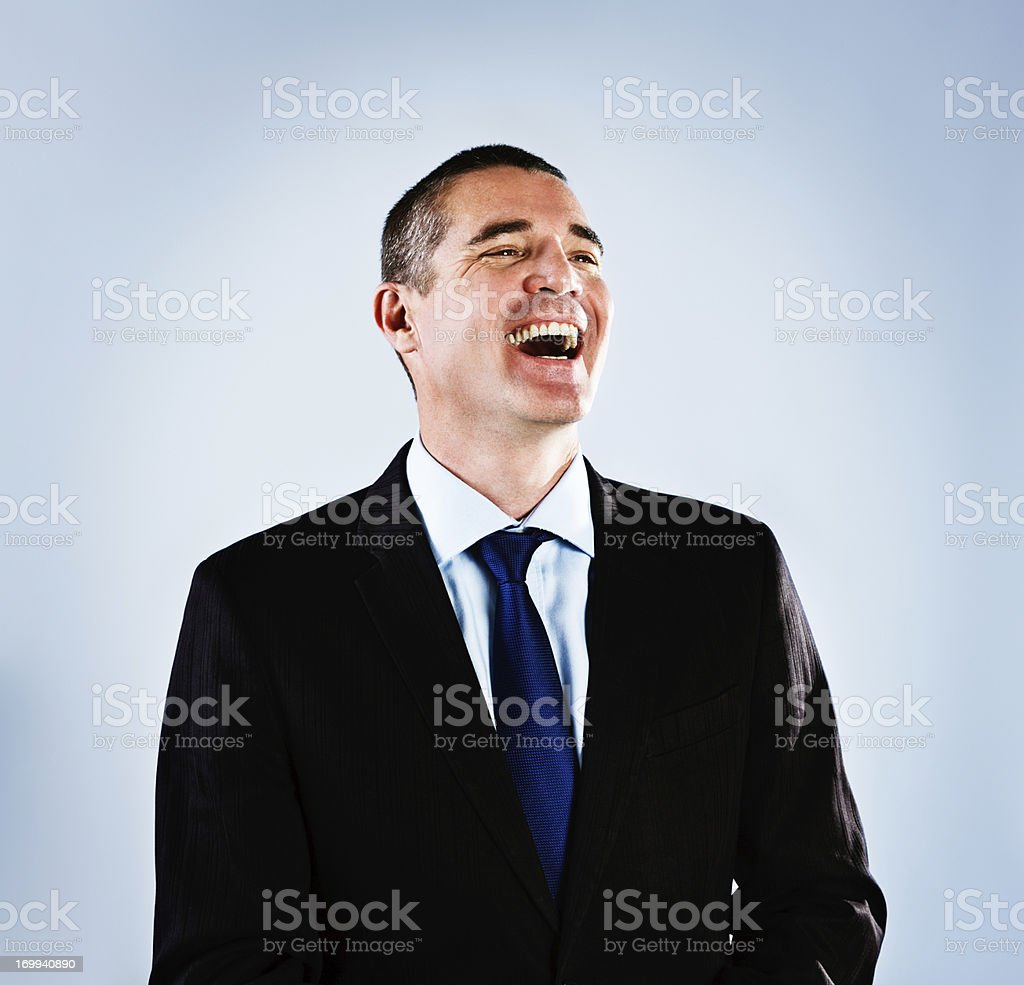 Delighted mature businessman laughs happily stock photo