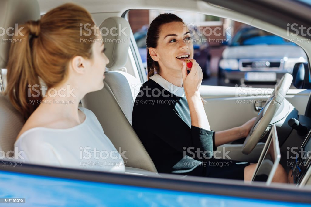 Delighted nice woman painting her lips stock photo