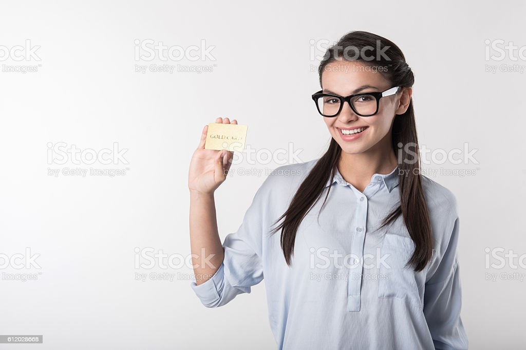 Delighted smiling woman holding gold card. stock photo