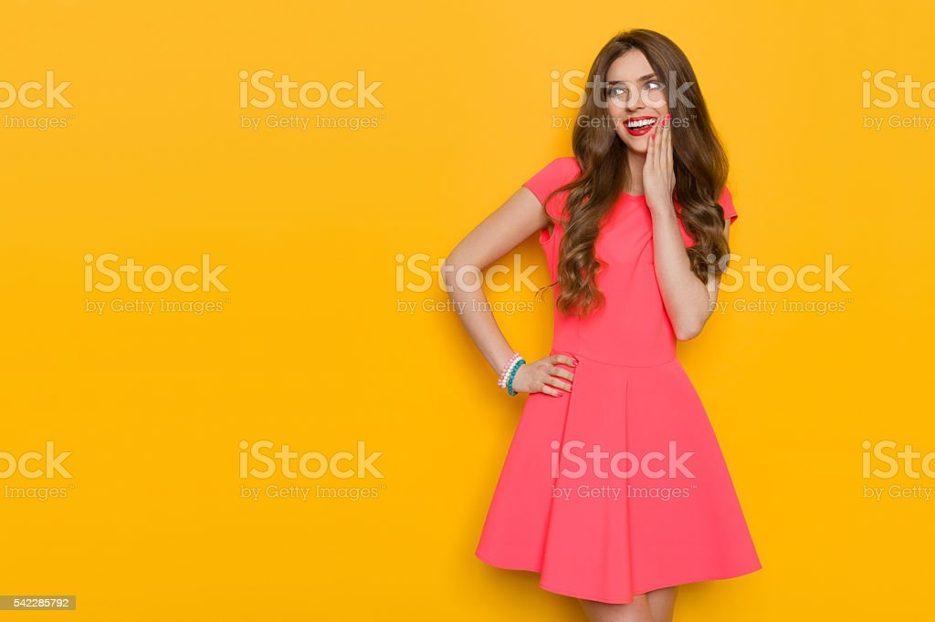 Delighted Woman In Pink Dress Looking Away stock photo