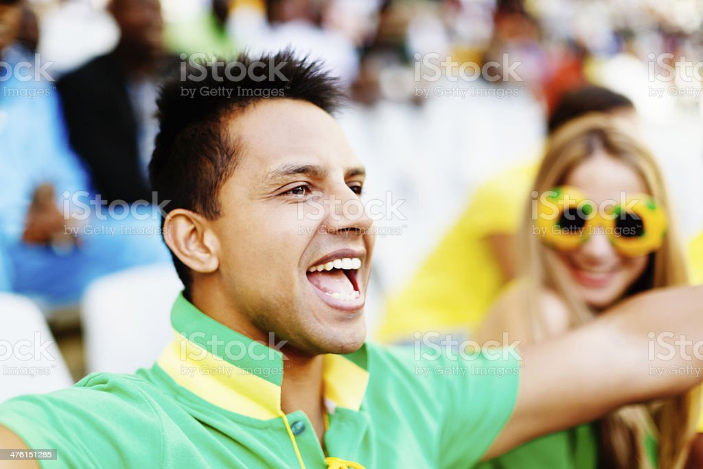 Delighted young man cheers on his soccer team, girlfriend watches royalty-free stock photo