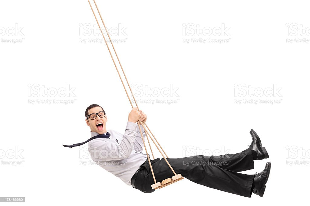 Delighted young man swinging on a swing stock photo