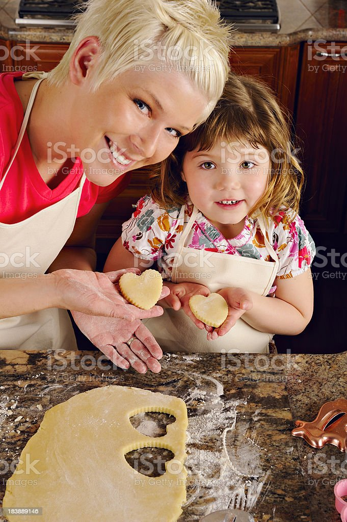 Delightful Mother Daughter Duo Holding Up Heart Shaped Cookies stock photo