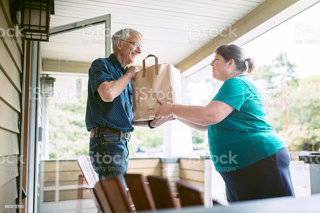 Delivering Groceries To Senior Man stock photo