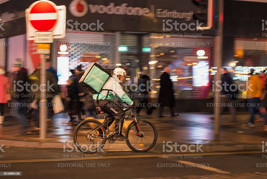 Deliveroo cyclist working at night stock photo