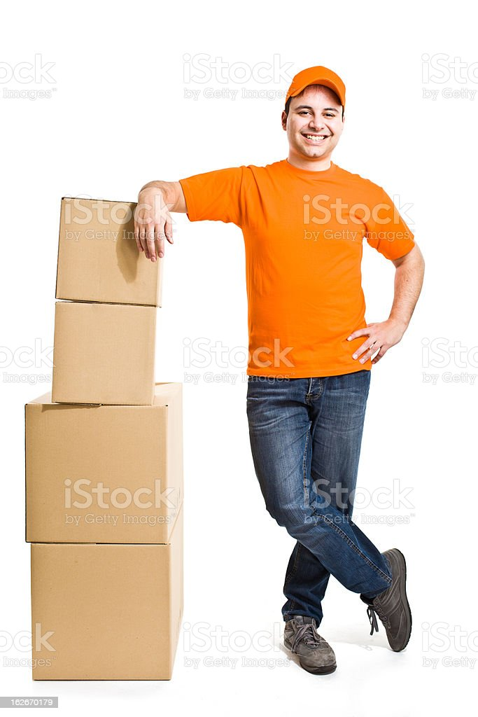 A delivery boy leaning on stacked boxes stock photo