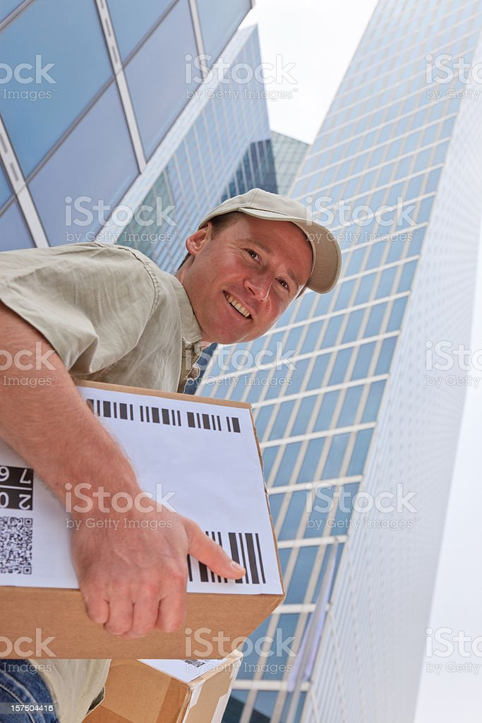 delivery boy standing in front of modern buildings royalty-free stock photo