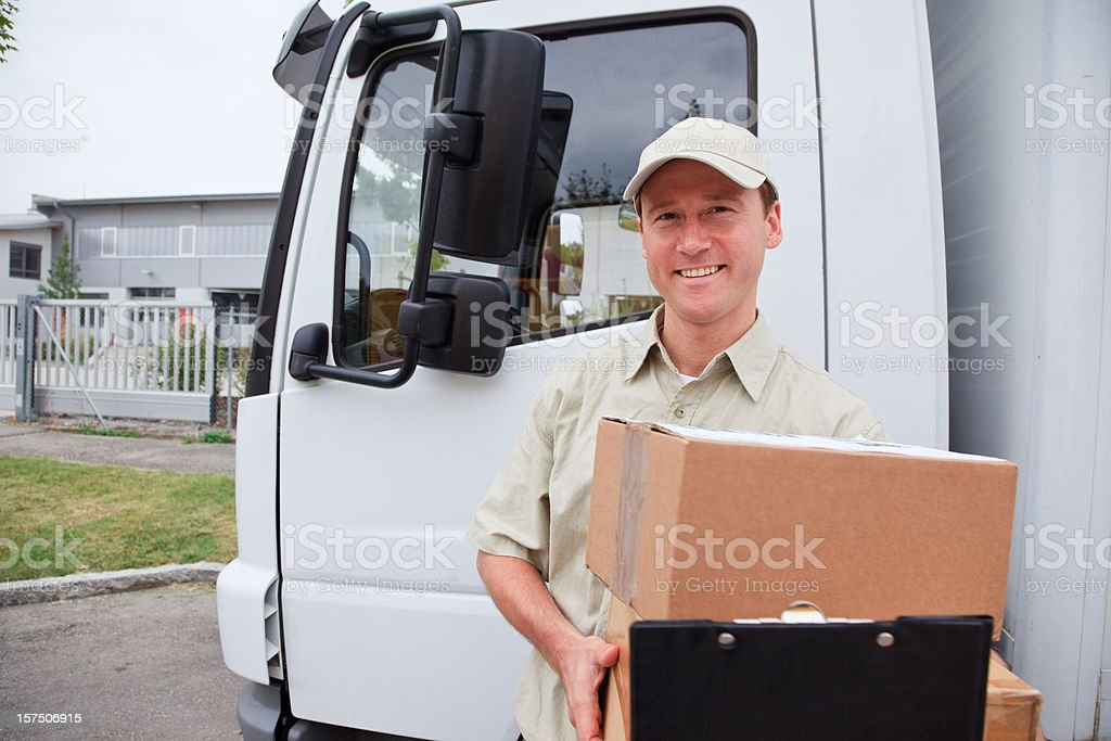 delivery boy standing next to a truck royalty-free stock photo