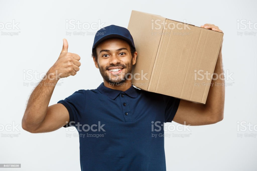 Delivery Concept - Portrait of Happy African American delivery man holding a box package and showing thumps up. Isolated on Grey studio Background. Copy Space. stock photo