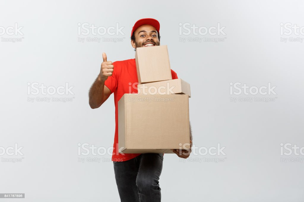 Delivery Concept - Portrait of Happy African American delivery man holding box packages and showing thumps up. Isolated on Grey studio Background. Copy Space. stock photo
