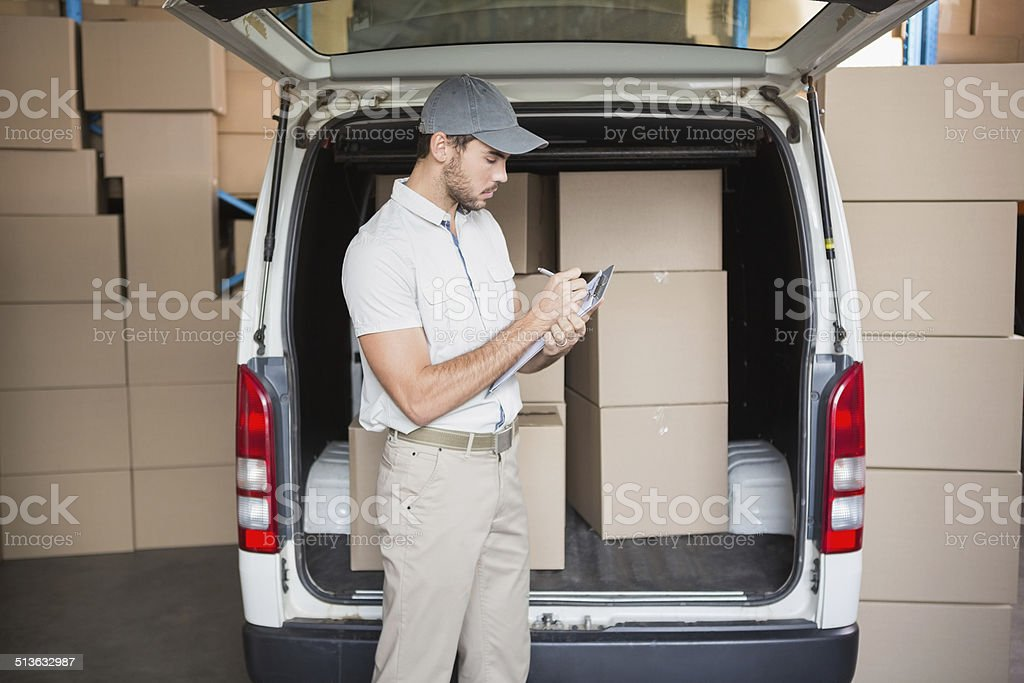 Delivery driver checking his list on clipboard stock photo