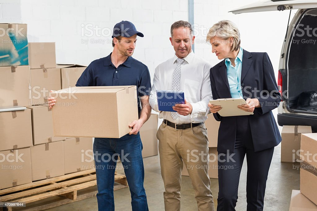 Delivery driver checking his list on tablet with managers stock photo