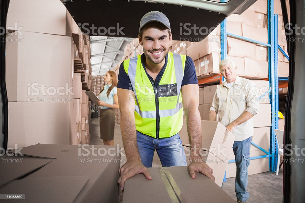 Delivery driver loading his van with boxes stock photo