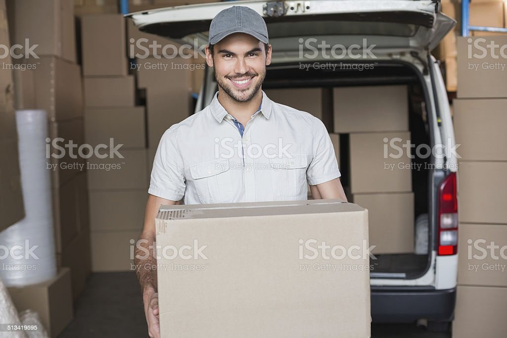 Delivery driver smiling at camera holding box stock photo