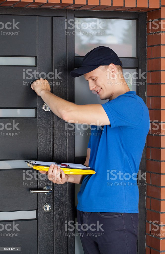 Delivery guy knocking on door stock photo