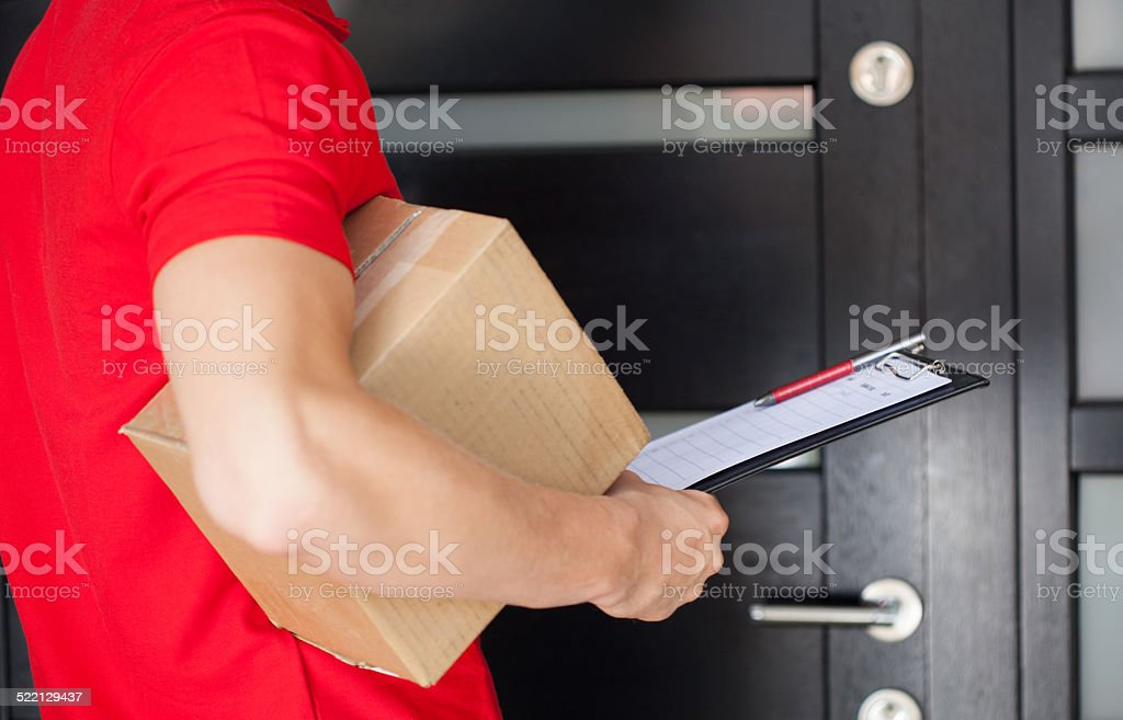 Delivery man at front door stock photo