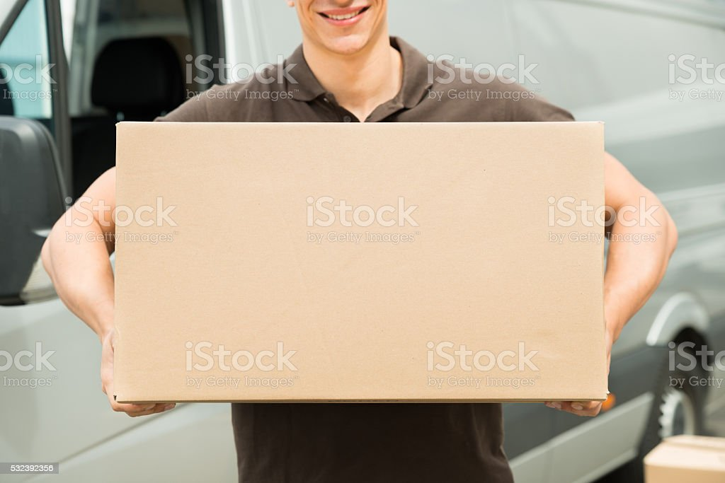 Delivery Man Carrying Box In Hand stock photo