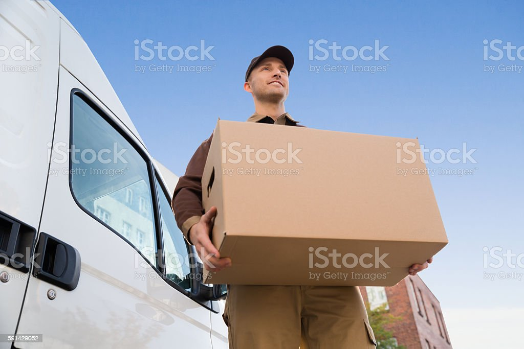 Delivery Man Carrying Cardboard Box By Truck Against Sky stock photo
