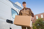 Delivery Man Carrying Cardboard Box By Truck