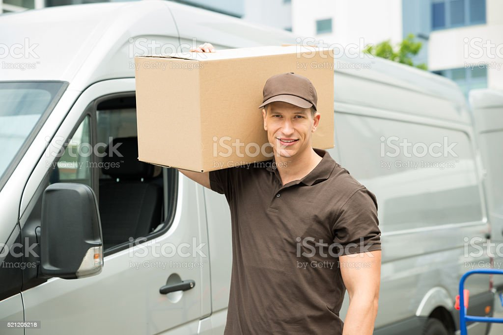 Delivery Man Carrying Cardboard Boxes stock photo